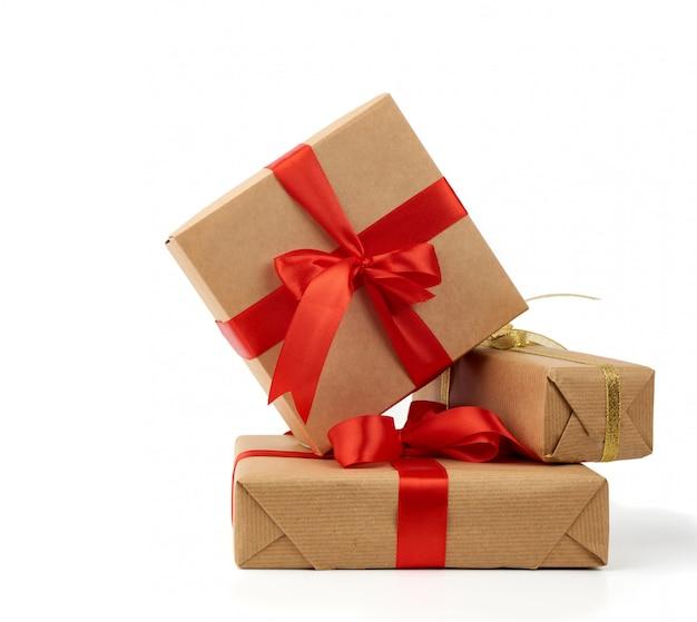 Стопка подарков, завернутая в коричневую крафт-бумагу и обвязанная шелковой лентой