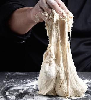 Шеф-повар в черной униформе замешивает тесто из белой пшеничной муки