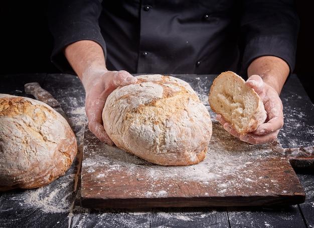 黒チュニックで調理する焼きたてのパンを保持しています