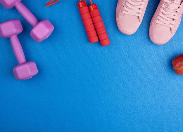 ピンクのスエードスニーカー、ダンベル、赤い縄跳びのペア