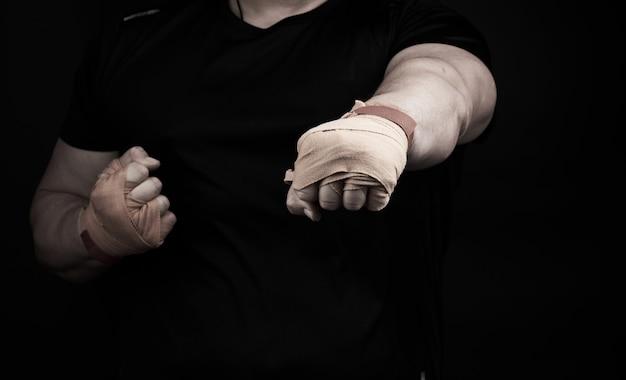Взрослый мужчина в черной форме и мускулистые руки стоит в спортивной позиции