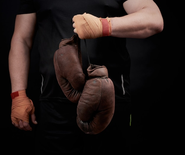 Мускулистый спортсмен в черной униформе держит в руке очень старые коричневые боксерские перчатки