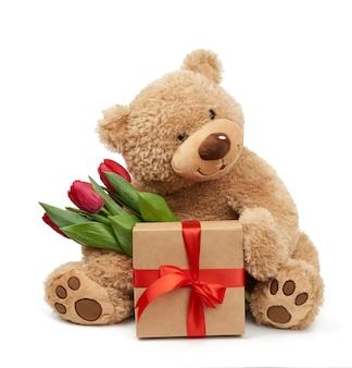 Милый коричневый мишка держит в лапке букет красных тюльпанов рядом с подарком