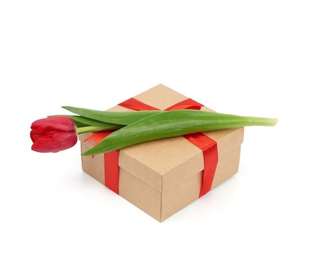 Квадратная коричневая коробка, обернутая красной шелковой лентой и красным цветущим тюльпаном