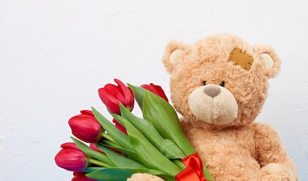 Милый коричневый мишка с заплатками держит в лапе букет красных тюльпанов