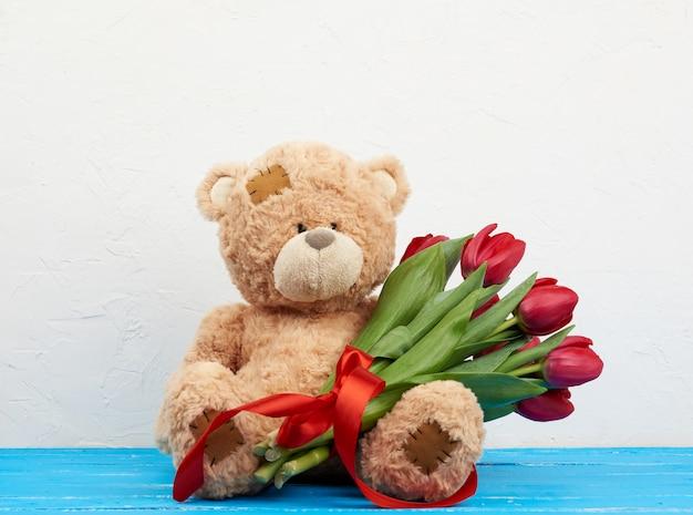 Милый коричневый мишка с заплатками сидит и держит в лапке букет красных тюльпанов