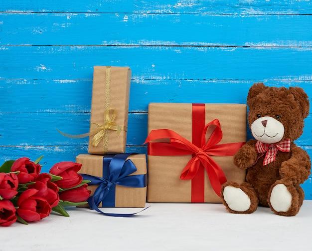 Симпатичный коричневый плюшевый мишка сидит, букет красных тюльпанов, красная коробка