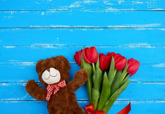 Милый коричневый мишка и букет из красных цветущих тюльпанов с зелеными стеблями и листьями