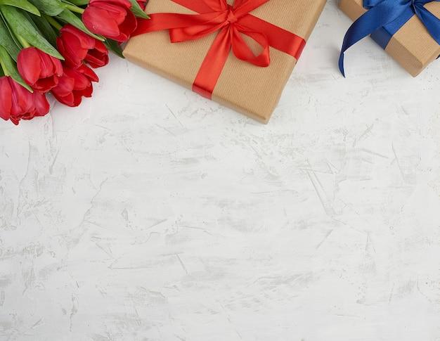 Букет из красных цветущих тюльпанов с зелеными листьями, завернутые подарки из коричневой крафт-бумаги и перевязанные шелковой лентой