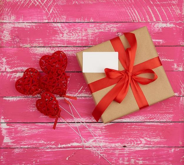 Прямоугольная коробка с подарком, перевязанная красной шелковой лентой и красными сердечками