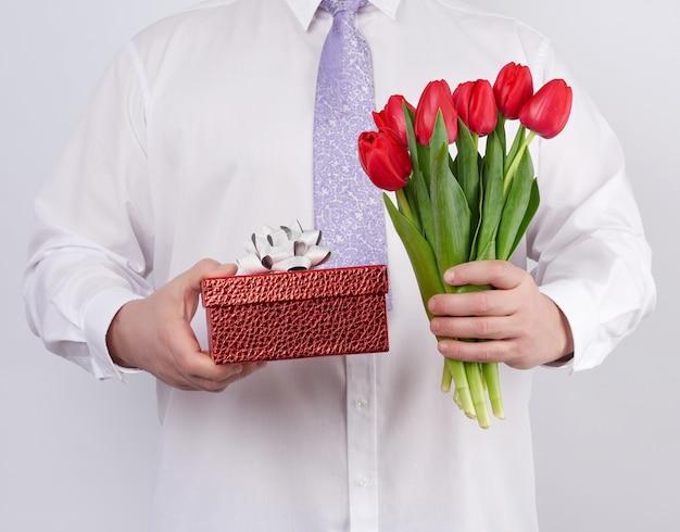 Мужчина в белой рубашке и сиреневом галстуке держит букет красных тюльпанов с зелеными листьями и подарочной коробкой