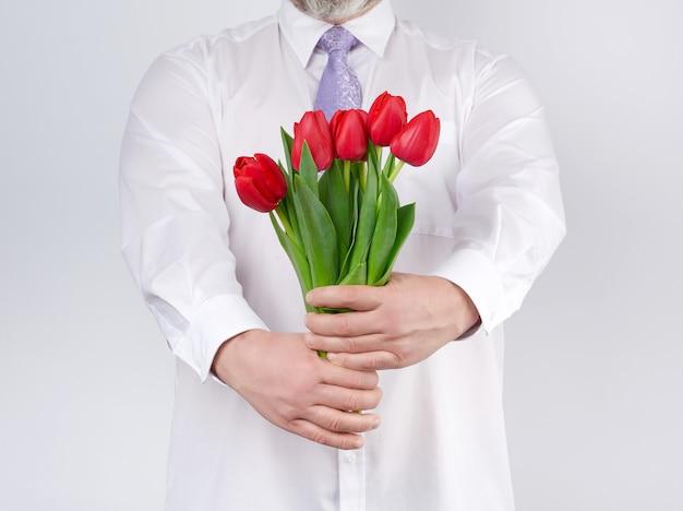 Взрослый мужчина в белой рубашке и сиреневом галстуке держит букет красных тюльпанов с зелеными листьями