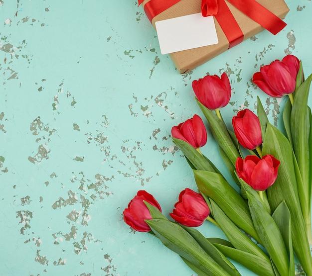 Букет из красных цветущих тюльпанов с зелеными листьями, завернутый в подарок из коричневой крафт-бумаги и перевязанный шелковой красной лентой