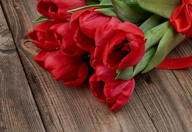 Букет из красных цветущих тюльпанов с зелеными стеблями и листьями, перевязанными красной шелковой лентой