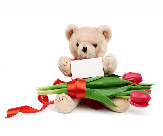Бежевый плюшевый мишка сидит с букетом красных цветущих тюльпанов и белой прямоугольной бумажной визиткой