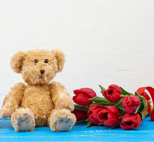 Милый коричневый мишка с букетом красных тюльпанов