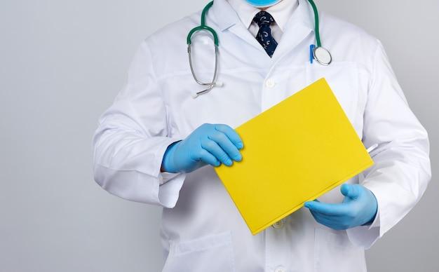 Мужской доктор в белом халате с кнопками держит желтую бумажную тетрадь