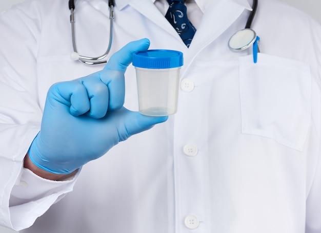 Мужской доктор в белом халате и галстуке стоит и держит пластиковый контейнер для образца мочи