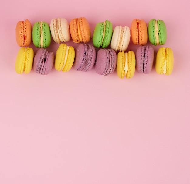 Желтые, фиолетовые круглые запеченные макароны на розовом столе, десерт лежит в ряд
