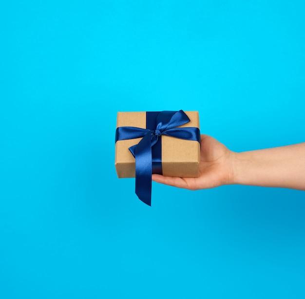 手は茶色のクラフトペーパーで包まれたシルクブルーのリボンで結ばれたギフトボックスを保持しています。