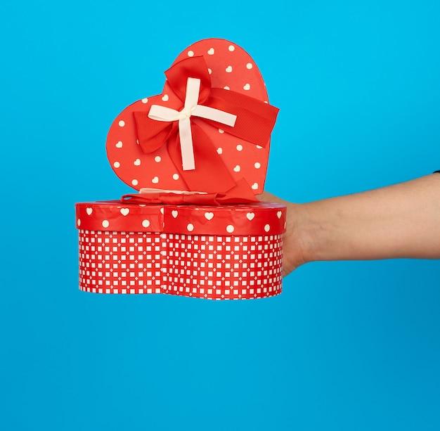 手はシルクのリボンが付いた赤いハート型の段ボール箱を持っています