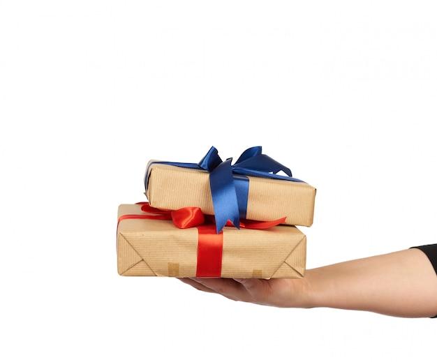 手は結ばれた絹の弓と茶色のクラフトペーパーで包まれた贈り物のスタックを保持しています。