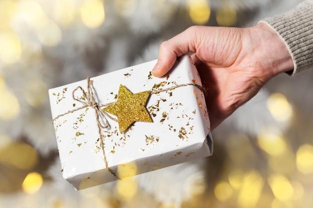 ゴールデンスター、クリスマスプレゼントと白いギフトボックスを持っている人間の手