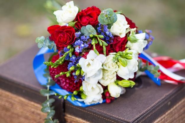 青いリボンで飾られた赤いバラと白いフリージアのウェディングブーケ