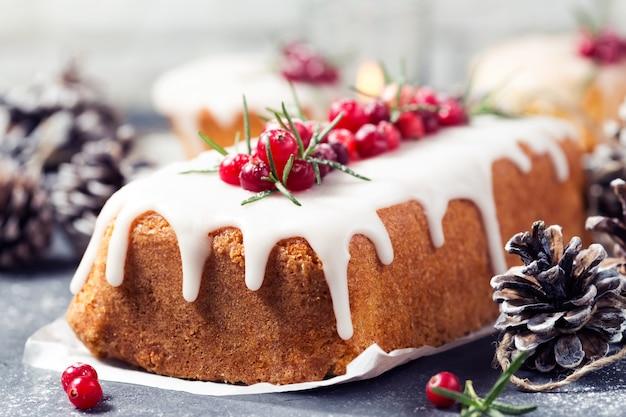 砂糖のアイシング、クランベリー、ローズマリーのクリスマスケーキ。