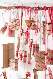 白い壁に掛かっている手作りのアドベントカレンダー。クラフト紙に包まれ、赤い糸とリボンで結ばれた贈り物。木製の棒と多くのプレゼント