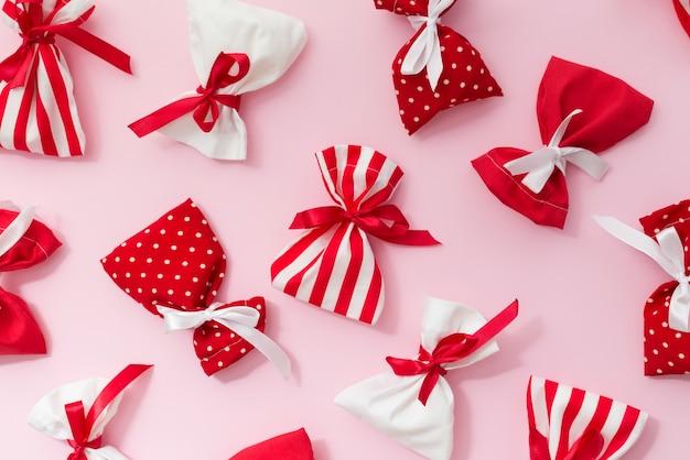 ギフトバッグで作られたクリスマスのパターン。赤と白のプレゼントとピンク。平置き