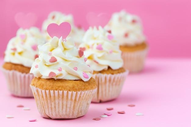 バレンタインデーのお菓子。ピンクの背景にカップケーキの装飾が施された心