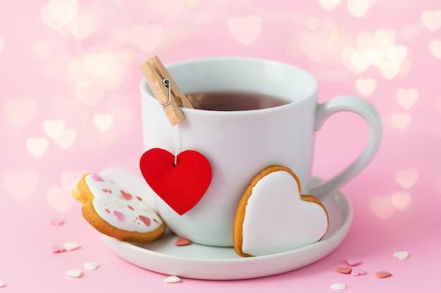 ボケ味の光でバレンタインデーの背景。赤いハートとクッキーとお茶のカップ