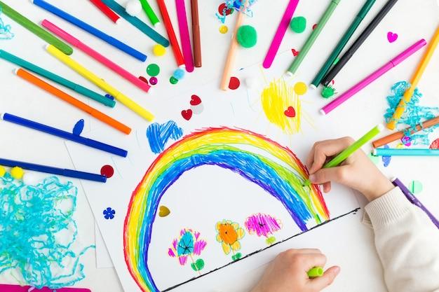 Ребенок рисует радугу с маркерами