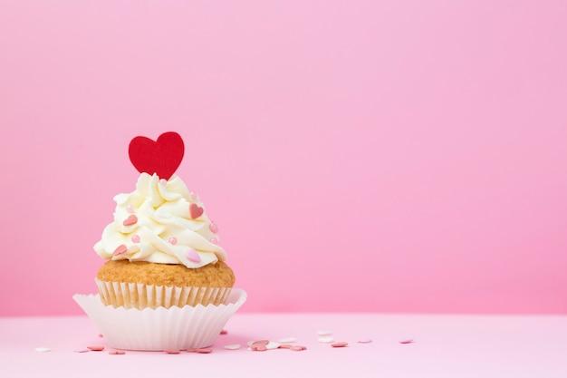 バレンタインデーのピンクの背景にカップケーキの装飾が施された心
