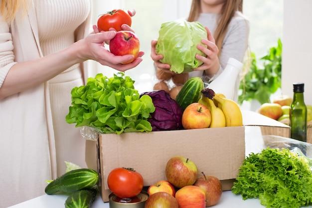 Доставка еды. мама и дочка распаковывают коробку с овощами и фруктами. онлайн заказ из продуктового магазина