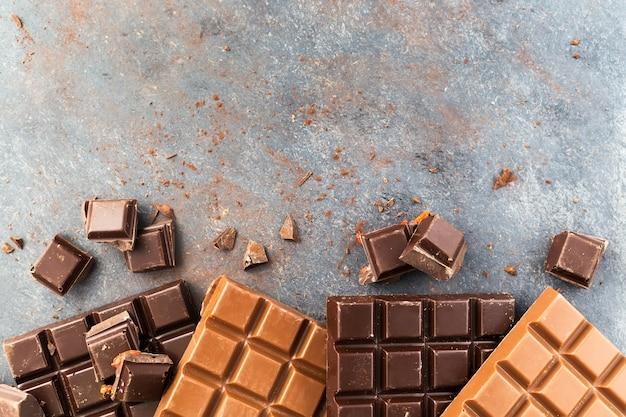 Молочные и темные шоколадные батончики на сером столе.
