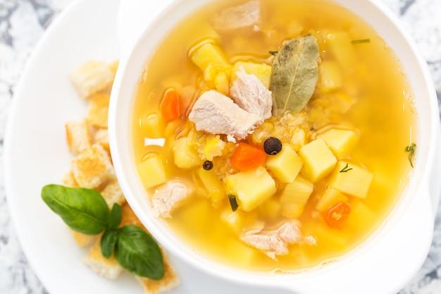 Суп из желтого гороха с куриным мясом в белой миске и тостами