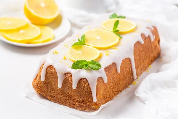 白い背景の上の砂糖のアイシングでレモンケーキ