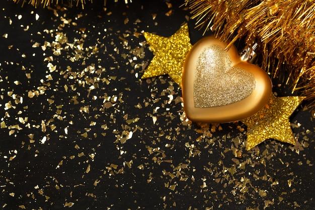 新年の背景、金色の星、クリスマスボール、キラキラ、黒いテーブル