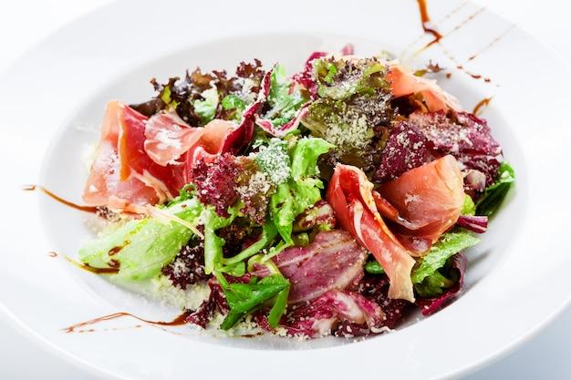 Ресторанный салат крупным планом с ветчиной и овощами
