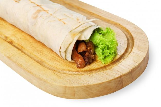 木製のデスクで豚肉と野菜のブリトー