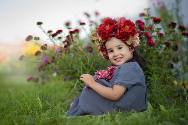 Маленькая девочка с красной цветочной короной сидит под цветущим кустом с бордовыми гвоздиками