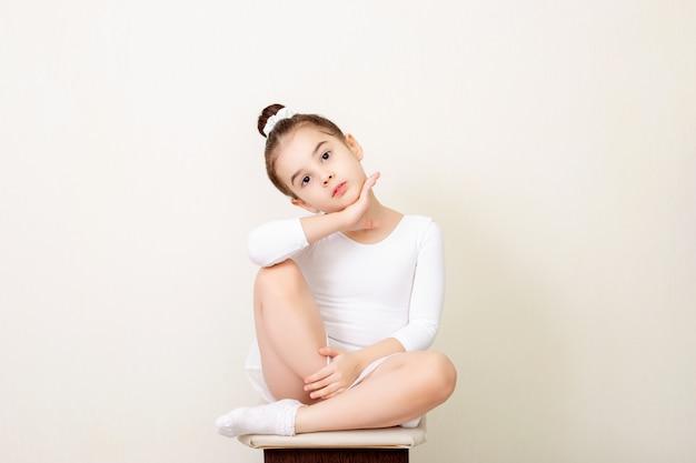 Красивая маленькая девочка красиво сидит в белом танцевальном купальнике