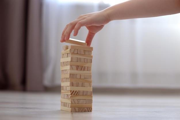 Детская рука собирает башню из деревянных блоков на полу.