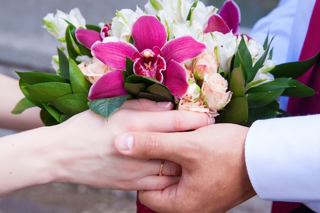 バラと蘭のウェディングブーケを持って恋人たち