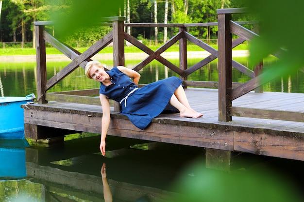 水の上の木製の桟橋に座っている美しい女性。手女性が水に触れます。水の近くの夏休み