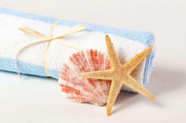 Морская звезда, морские раковины и полотенца на белом