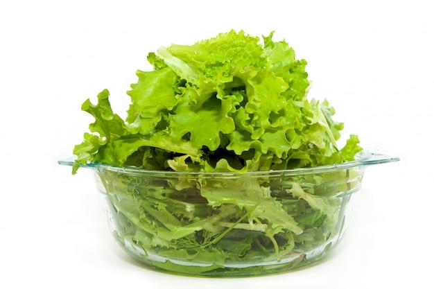 Свежий зеленый салат в стеклянной миске на белом фоне