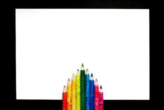 一枚の紙にカラフルな鉛筆が美しく横たわる